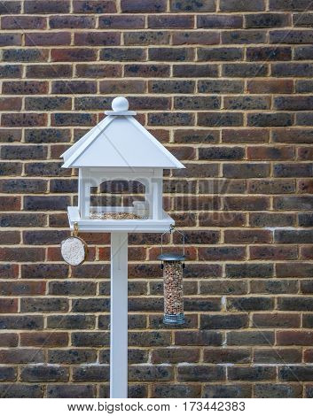 Newly set up bird table set against a brick wall and with a nut holder and coconut and seeds on the table. The bird table has a white pointed roof.