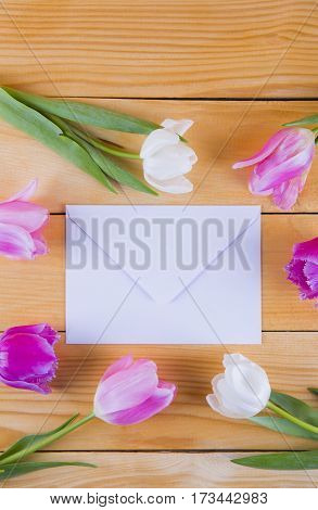 Bouquet Of Tender Pink Tulips With White Envelope On Light Wooden Background