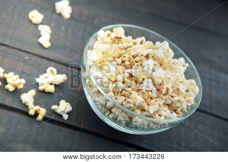 Glass Bowl With Freshly Popped Popcorn With Salt On Dark Wooden Background. Soft Focus.