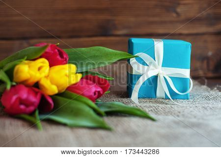 Beautiful tulips and blue gift on wooden background. Concept of holiday birthday Easter March 8.
