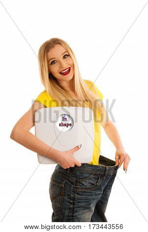 Happy Womman Holding A Scale And Too Big Trousers As She Lost Weight Isolated Over White Background