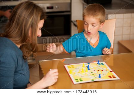 mother and kid playing ludo game in living room
