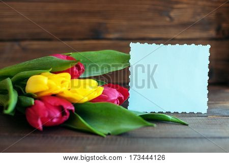 Flowers and a welcome card on dark wooden background. Concept of holiday birthday Easter March 8.