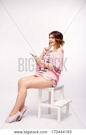 Beautiful pregnant woman is using a digital tablet while sitting on the chair