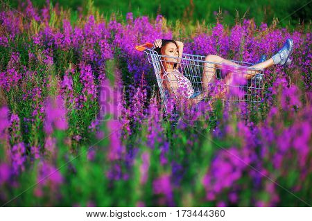Beautiful dark-haired girl student in a t-shirt and short shorts got in the cart from the store in the middle of a clearing beautiful flowers of fireweed quietly enjoying the sun on her face.