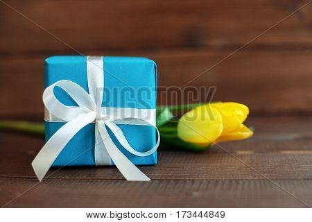 Flower and blue gift on dark wooden background. Concept of holiday birthday Easter March 8.