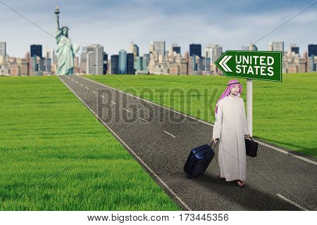 Portrait of Muslim businessman getting out from the city with text of United States on a signpost while carrying a suitcase and a briefcase