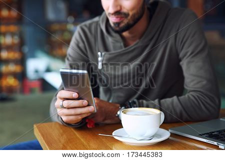 Cheerful hipster guy at the restaurant using a mobile phone, hands close up