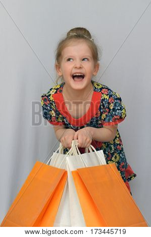 The little girl, the buyer holds the colored shopping bags.