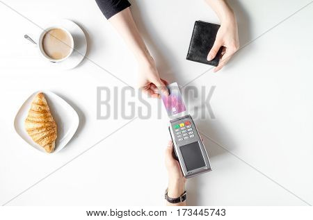 Payment by credit card for business break in cafe on white table background top view