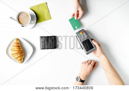 Credit card payment bill in cafe for croissant and coffee on white table background top view