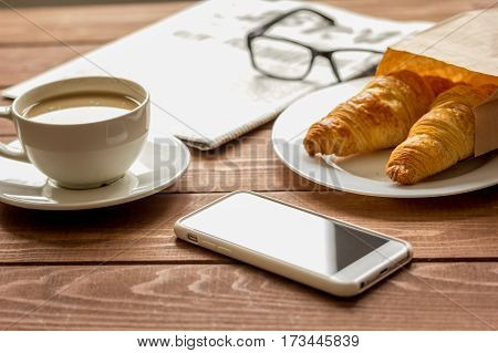 Business cup of coffee with croisant, morning newspaper, glasses and mobile phone on wooden desk