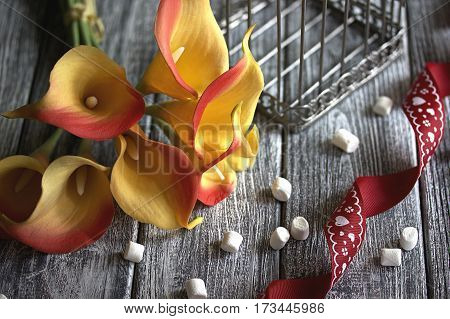 Orange Yellow Calla Lilies With Red Ribbon And White Marshmallows On Wooden Gray Background