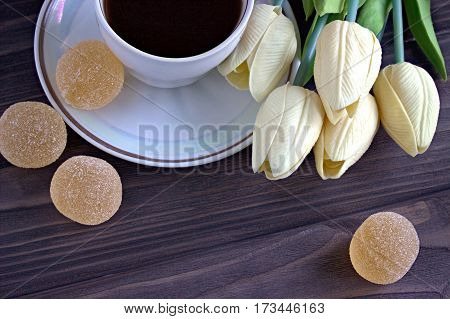 Marmalade And A Cup Of Coffee With A Bouquet Of Yellow Tulips On A Brown Wooden Background. Coffee P