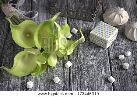 Bouquet Of Green Yellow Calla Lilies With Marshmallows And Cardboard Box On A Gray Wooden Background