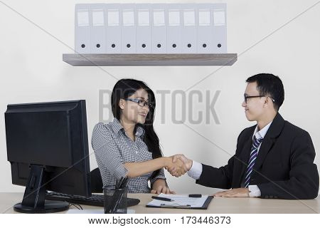 Young male manager giving a congrats sign by shaking hands on new employee while sitting in the office room with computer and clipboard on the desk