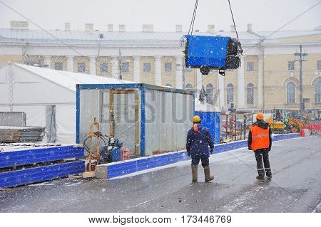 Two men in overalls and hard hats supervise the unloading of equipment for installation in the centre of town during a snowfall.