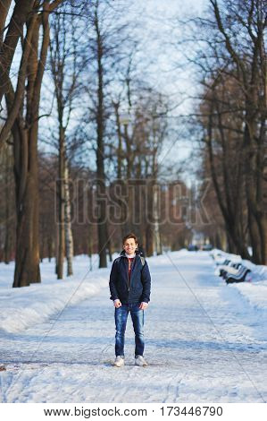 Young smiling man walks through the snowy Park on a clear winter day