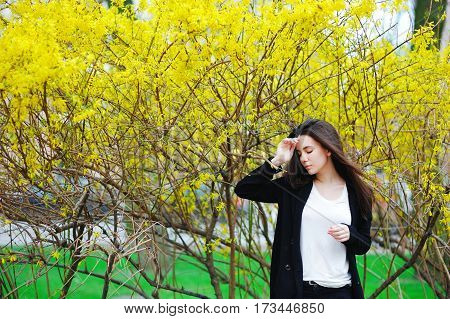 Outdoor portrait of young beautiful fashionable lady posing near flowering tree. Female beauty fashion. City lifestyle.
