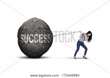 Beautiful businesswoman dragging big stone with success word isolated on white background
