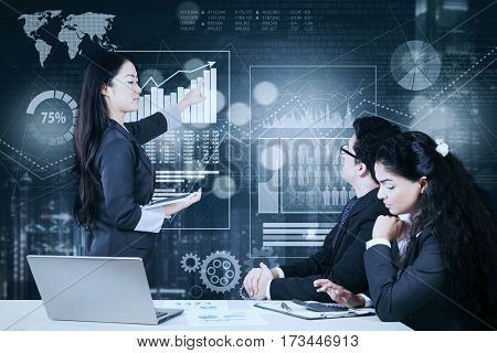Asian businesswoman pointing a virtual screen to deliver a presentation and explaining business solutions to her partners