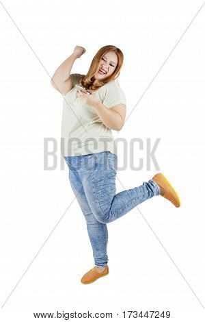 Full length of obese girl with blonde hair reading sms message on her mobile phone and looks happy. Isolated on white background