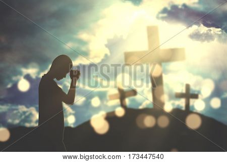 Silhouette of a devout christian man worships to the GOD with three cross signs and sunlight on the sky