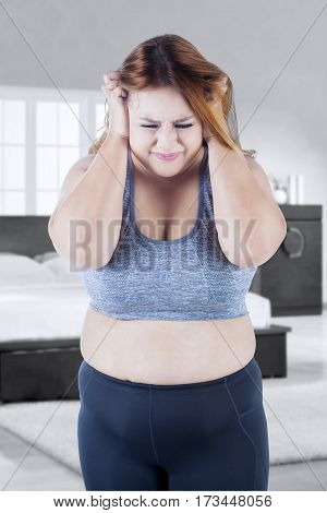 Photo of overweight woman looks depressed standing in the bedroom while scratching her head