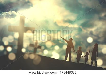 Silhouette of family walking on the hill towards three crucifix symbols with bright sunlight on the sky