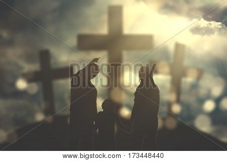 Silhouette of family looking at three cross symbols with bright sunlight on the sky