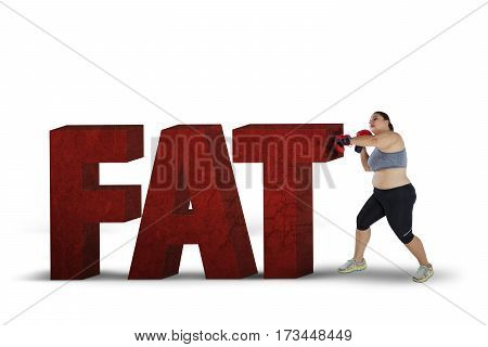 Overweight woman wearing boxing gloves while fighting with stones shaped word of fat on the studio