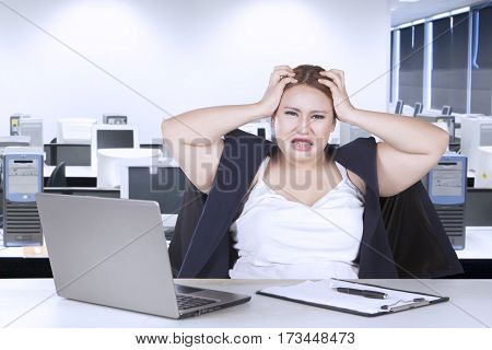 Portrait of fat woman frustration with job and holding her head while sitting in front of laptop