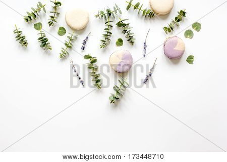 Colorful macaroons and eucalyptus on woman table flat lay top view mock up