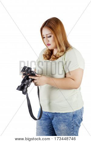 Image of female photographer holding a digital camera while looking at a photo on the camera screen isolated on white background