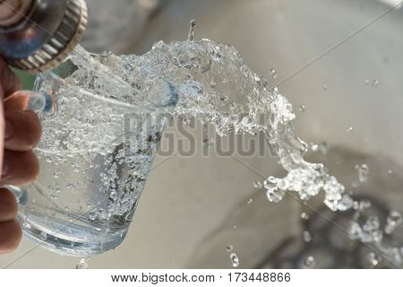 water splash from glass with female hand.