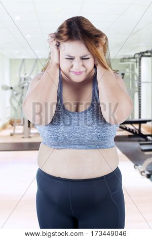 Picture of overweight woman looks frustrated standing in the fitness center while scratching her head