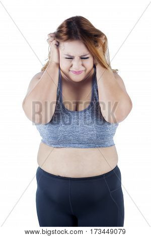 Portrait of frustrated overweight woman standing in the studio while scratching head and wearing sportswear