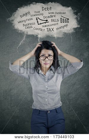 Photo of a young businesswoman looks frustrated thinking her problems under cloud speech bubble