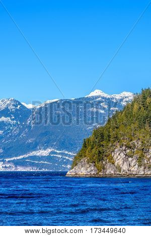 Fantastic view over ocean, snow mountain and rocks at Furry Creek Dive Site in Vancouver, Canada.