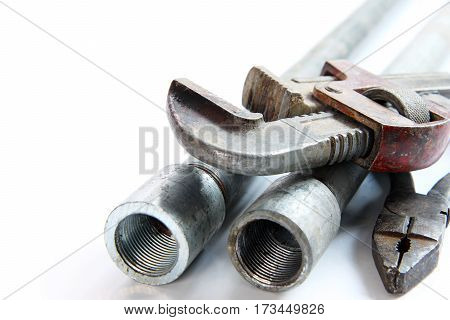 pipe alligator wrench pliers and steel pipes on white background