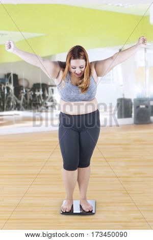 Portrait of happy overweight woman with blonde hair expressing her success while standing on a weighing scale at gym
