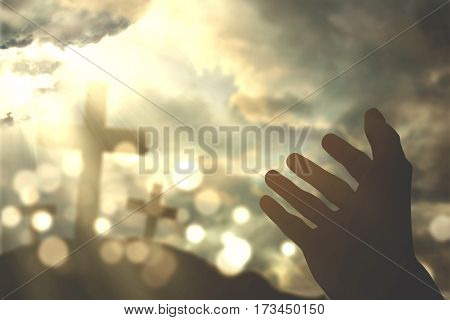 Picture of human hands praying to the GOD with christian cross symbol and bright sunlight on the sky
