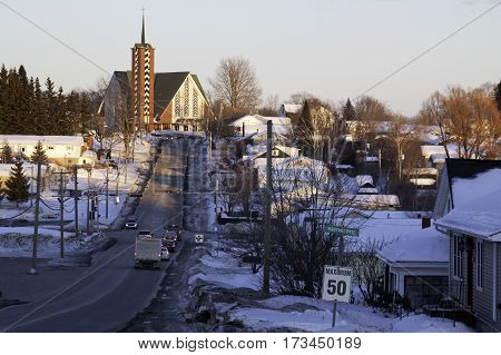 Wide view of a long street with vehicles leading up a hill to a church at the top with a houses and buildings on either side in Bathurst New Brunswick on a bright sunny day with blue skies and clouds in February.