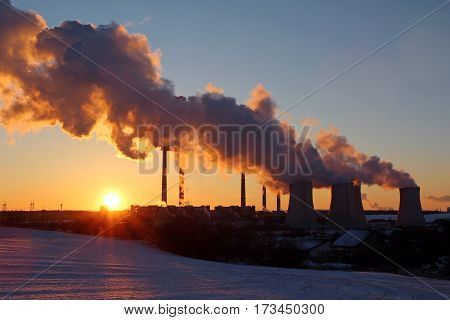 winter landscape during sunset with steaming factory