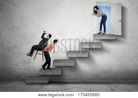 Female manager commanding her employees through a megaphone to walk upward on the stair