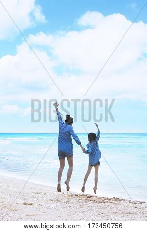 Back view of mother and daughter having fun while leaping on the beach