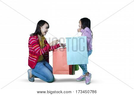 mage of young mother and daughter opening shopping bags isolated on white background