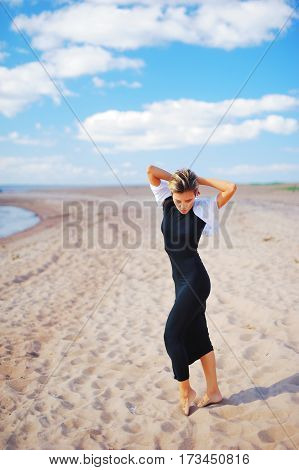 Portrait of a young slender girl model in black dress posing barefoot on a sandy beach on the seafront on a Sunny day for advertising in a fashion magazine.