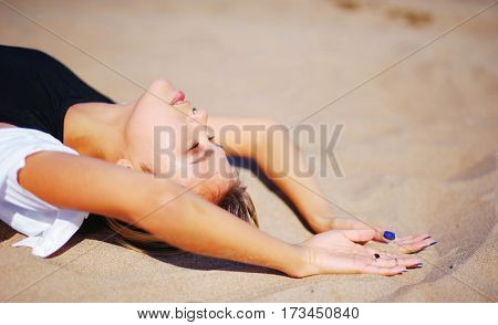 young beautiful brunette girl in black dress relaxes on the sand eyes closed and hands outstretched palms up close-up