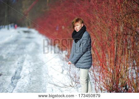 Portrait of a young pretty girl with fair-haired hair no hat warm clothes in winter forest near the road on a clear Sunny day.